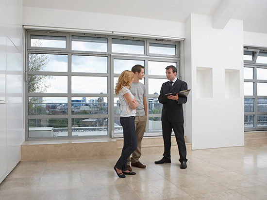 Real Estate Agent Showing Property to New Buyers